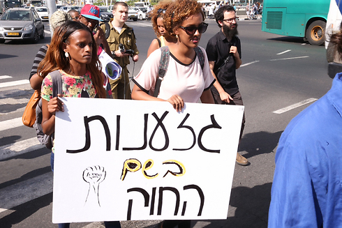 Protesters hold sign saying 'Racism in the name of the law' (Photo: Motti Kimchi)
