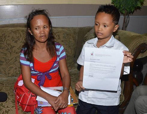 """לצד אמו, """"לא היה לי כסף לתת לו לארוחת צהריים"""" (צילום: AFP)"""