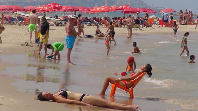 מנסים להתקרר בחוף הים של תל אביב (צילום: ג'ורג' גינסברג)