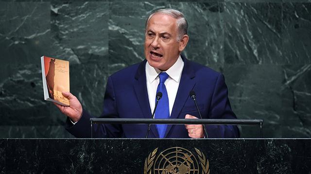 Prime Minister Benjamin Netanyahu holding Ali Khamenei's new book (Photo: AFP)