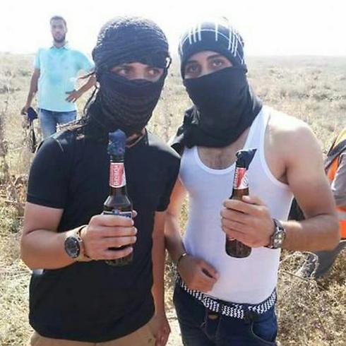 אחמד על הרבאווי (משמאל) עם בקבוק תבערה רגע לפני שנורה בעימותים בעזה ()