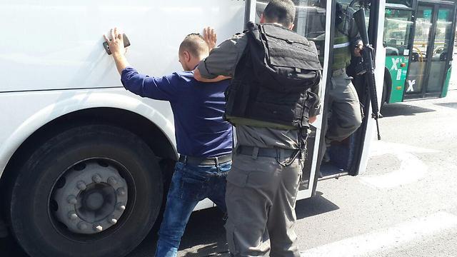 Border policeman frisks Arab man in East Jerusalem (Photo: Elior Levy)