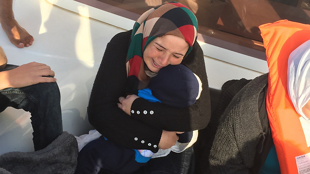 Syrian refugee on yacht holding her dead baby (Photo: Gal Baruch)