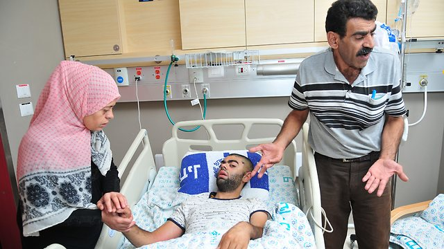 Mohammed Ziada's parents at his bedside. (Photo: Rafi Kotz)