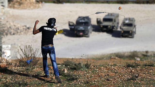 Palestinian rioters throw rocks at troops (Photo: AFP)