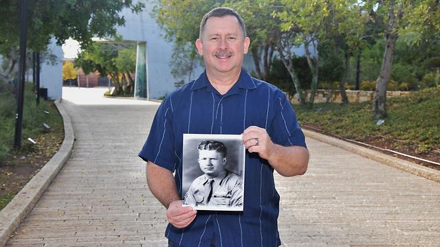 """כריס אדמונדס עם תמונת אביו ביד ושם. """"לקח סיכון אישי כדי להגן על אחרים"""" ()"""