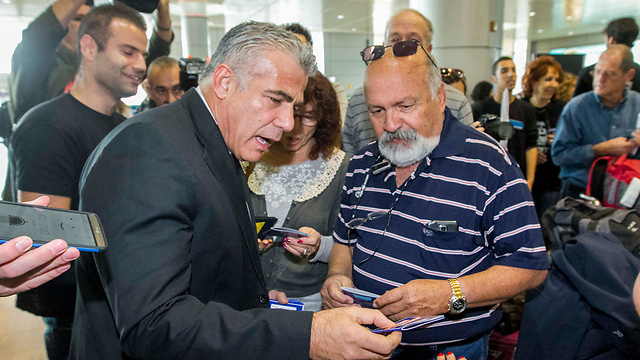 MK Yair Lapid handing out anti-BDS fliers at Ben Gurion Airport. (Photo: Ido Erez)
