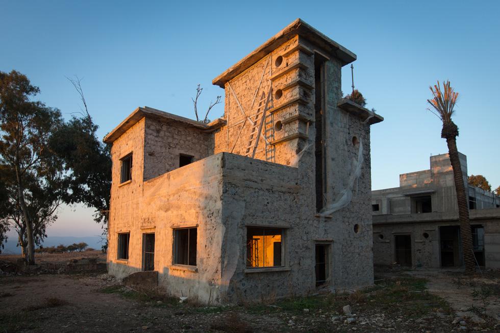 אחד הבניינים ההיסטוריים, לימינו האורווה הצרה שתהפוך לפאב, ומעבר לה בית ההארחה החדש ( צילום: דור נבו )