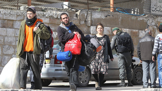 Settlers with their possessions after being evicted from two houses in Hebron by IDF troops (Photo: AFP)