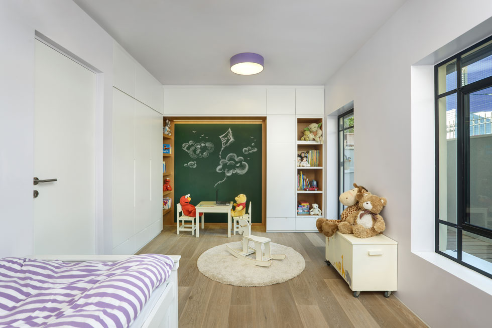 גם לחדר הילדים חצר פנימית משלו, מכוסה בדק ומוצלת היטב. ארון הקיר ממסגר לוח גיר גדול ופינת יצירה ( צילום: ארקדי רסקין ואלכס פרלמן )