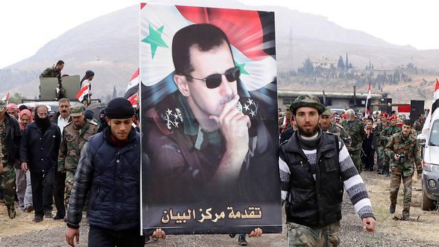 Syrians hold poster of Bashar Assad (Photo: AFP)