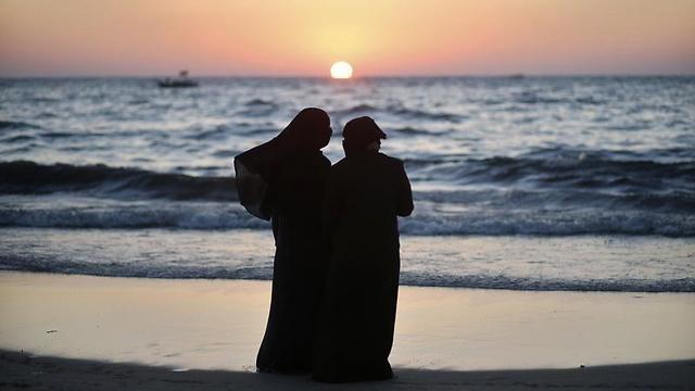 Palestinian women stand on a beach in Gaza City during sunset on summer's day (Photo: Reuters/Archive)