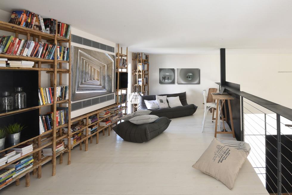 נוימן עיצבה את המעקה שמלווה את גרם המדרגות ממוטות במבוק, וכך גם את הספרייה שבגלריה מעל המטבח (צילום: עמית גושר)