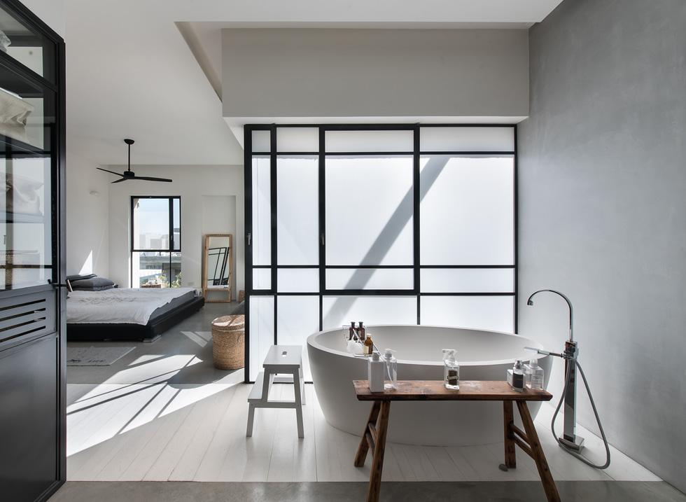 חדר ההורים שבקומה העליונה. המיטה פונה אל מרפסת גדולה, והאמבטיה עומדת בחלל בחופשיות. בצד יש מקלחון ושירותים סגורים (צילום: עמית גושר)