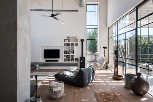 הסלון: ספות רביצה אפורות וכורסה שקופה התלויה מהתקרה  (צילום: עמית גושר)