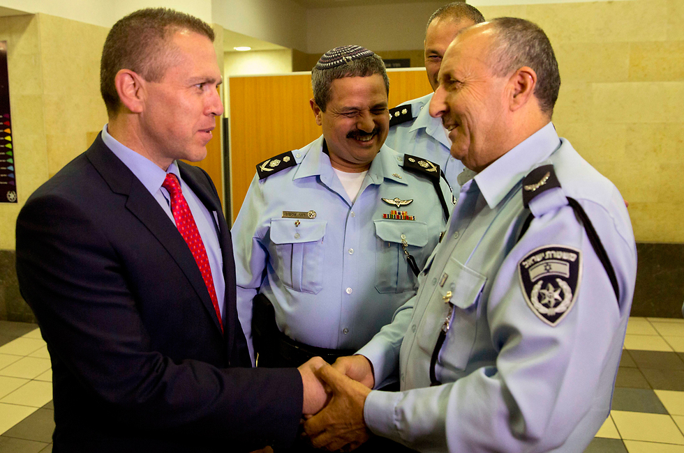 Gilad Erdan shakes hands with Gamal Hakroosh as he is appointed Northern Police Commissioner (Photo: AP)
