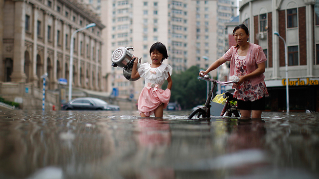 עשרות נהרגו. תושבים בעיר סינית מוצפת (צילום: AP)