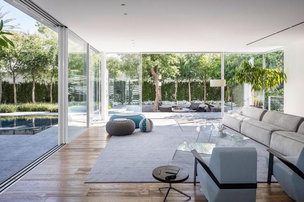 הסלון פונה לבריכת השחייה ולפינת ישיבה אינטימית שנחפרה בחצר בגובה נמוך מפני הקרקע, ובמרכזה קמין עצים (צילום: עמית גרון)