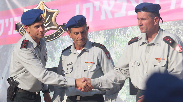 Outgoing CID commander Col. Erez Raban, left, shakes the hand of incoming CID commander Col. Gil Mamon (Photo: Motti Kimchi)