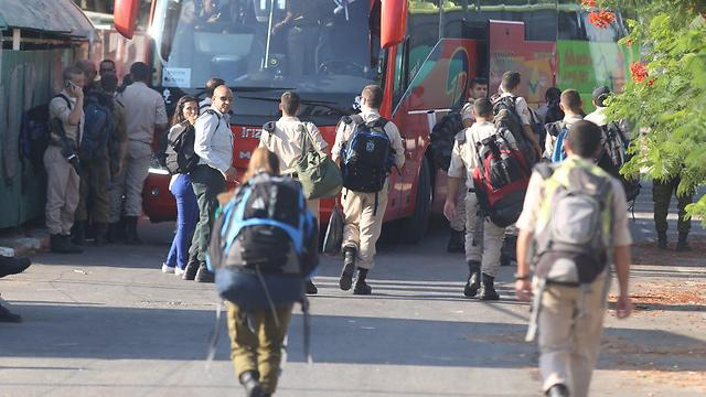 Soldiers scramble for the bus to arrive on time to their bases (Photo: Motti Kimchi)