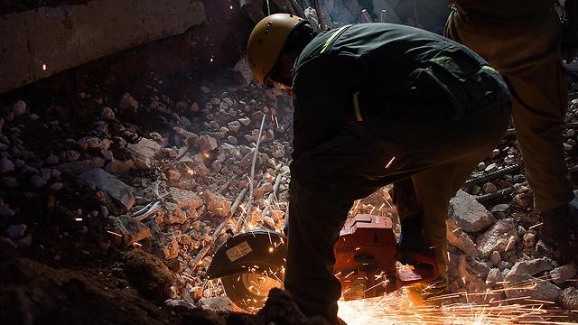 Rescue worker using a buzzsaw to cut through debris (Photo: IDF Spokesman)