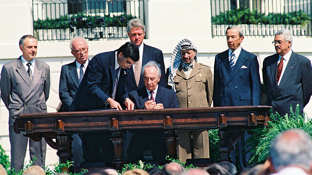Peres, sitting, signing the Oslo Accords with Palestinian leader Yasser Arafat, US President Bill Clinton and Israeli Prime Minister Yitzhak Rabin looking on (Photo: Avi Ohayon, GPO)