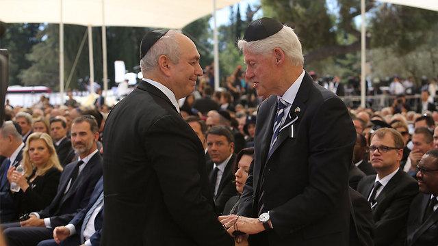 Former US President Bill Clinton comforting Chemi Peres (Photo: Gil Yohanan)