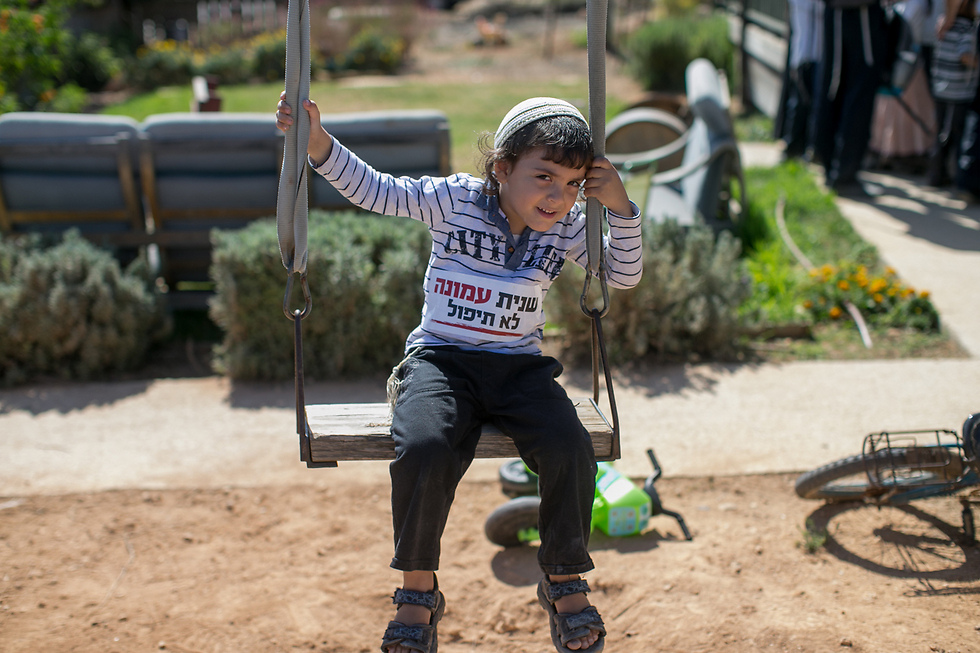 A child in Ofra with a sticker on his shirt saying 'Ofra will not fall again' (Photo: Ohad Zwigenberg)