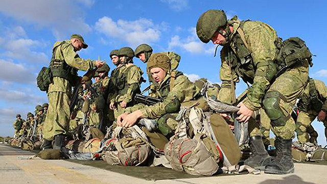 Russian paratroopers prepare their parachutes