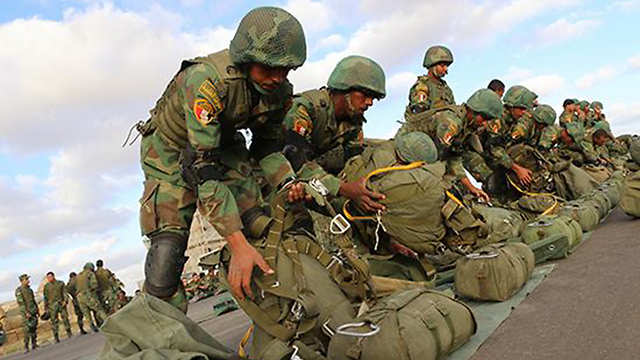 Egyptian paratroopers prepare their parachutes