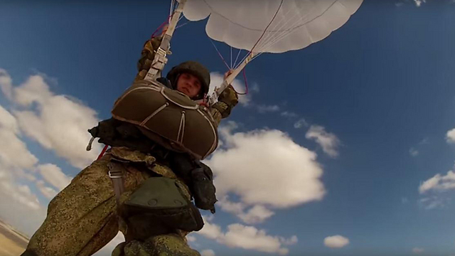 A Russian paratroopers floats down to the ground