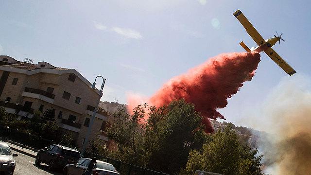 מטוס מטיל חומר מעכב בעירה על בתים שנשרפו בחיפה (צילום: AFP)