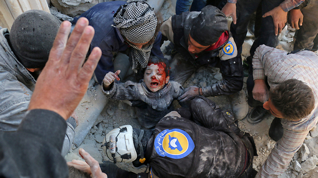 A wounded child being pulled out of the rubble in Aleppo (Photo: AFP)
