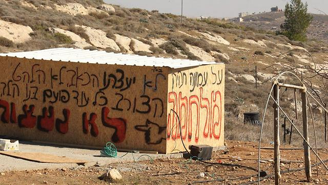 A building in the settlement of Amona, grafittied with signs of resistence to the evacuation (Photo: Motti Kimchi)