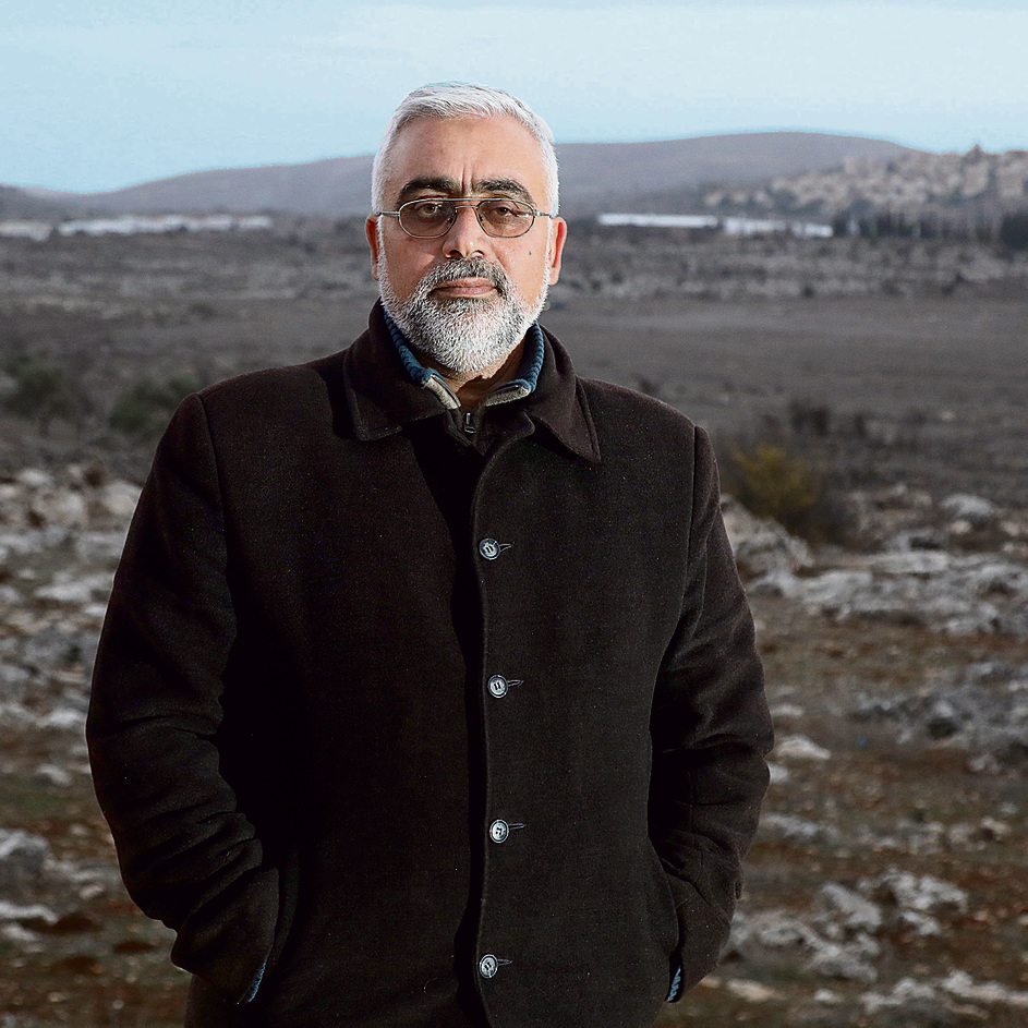 Hazem Hassim Ajaj against the backdrop of Amona. 'I don't want any compensation. Money comes and goes, but the land stays' (Photo: Shaul Golan)