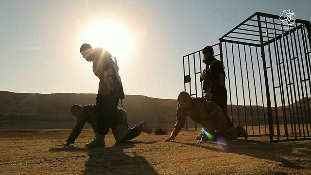 ISIS fighters leading Turkish soldiers out of their cage to their execution spot