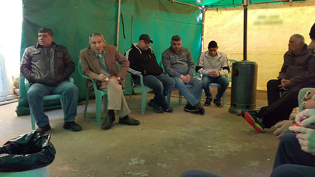 Family sits in a mourning tent