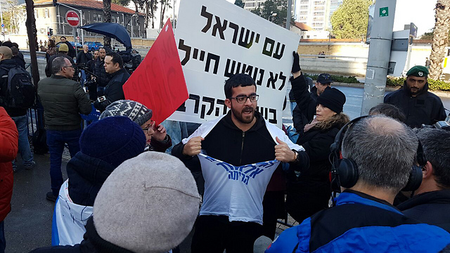 A protester tearing a shirt, with a sign that says 'The people of Israel don't abandon a soldier during battle' (Photo: TPS)