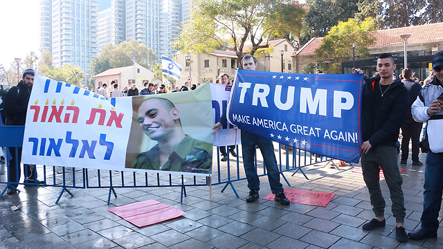 Protesters with a sign with Elor's picture saying 'Giving the light back to Elor' alongside a Trump support sign (Photo: Dana Kopel)