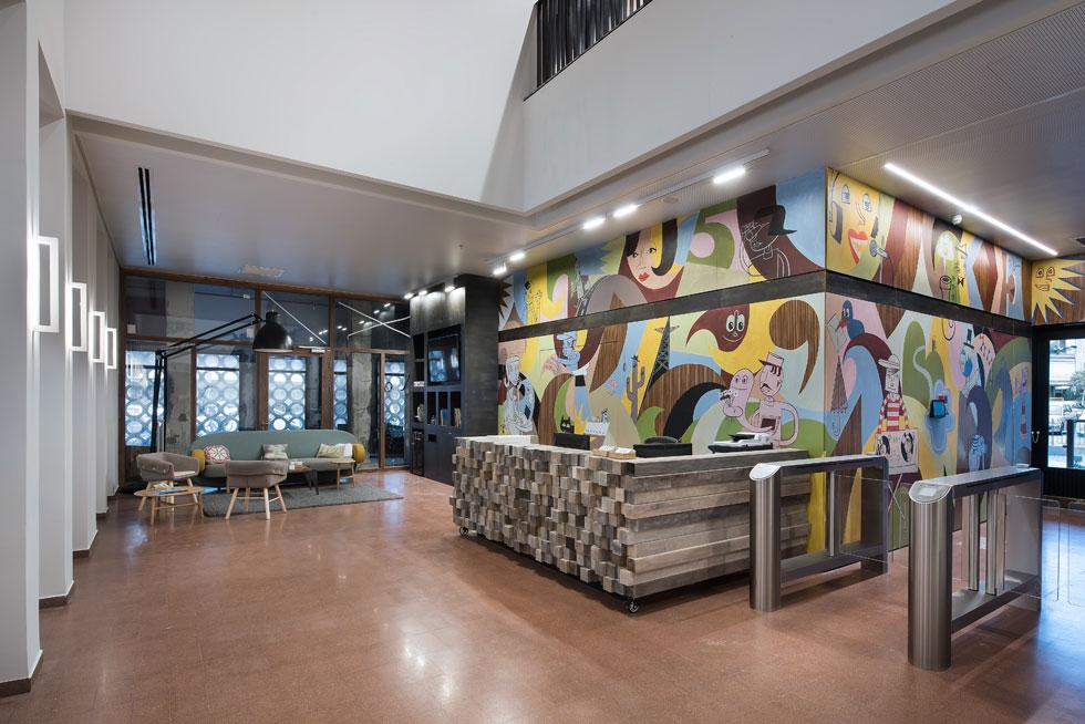 לובי הכניסה. קירות העץ המקוריים שומרו בשיפוץ הבניין, והם מבצבצים מבעד לקיר גרפיטי של האמן הגרמני ג'ים אביניון. דלפק הקבלה עשוי עץ ממוחזר, שחוזר כאלמנט קבוע בקומות המשרדים, ועל הכריות של הספה הדפסים שנקנו ממעצבי הקהילה (צילום: עמית גושר)