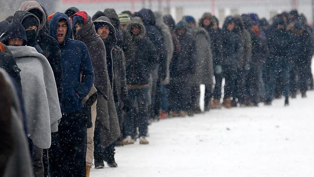 מהגרים חסרי בית בבלגרד בתור ארוך לאוכל (צילום: AP)