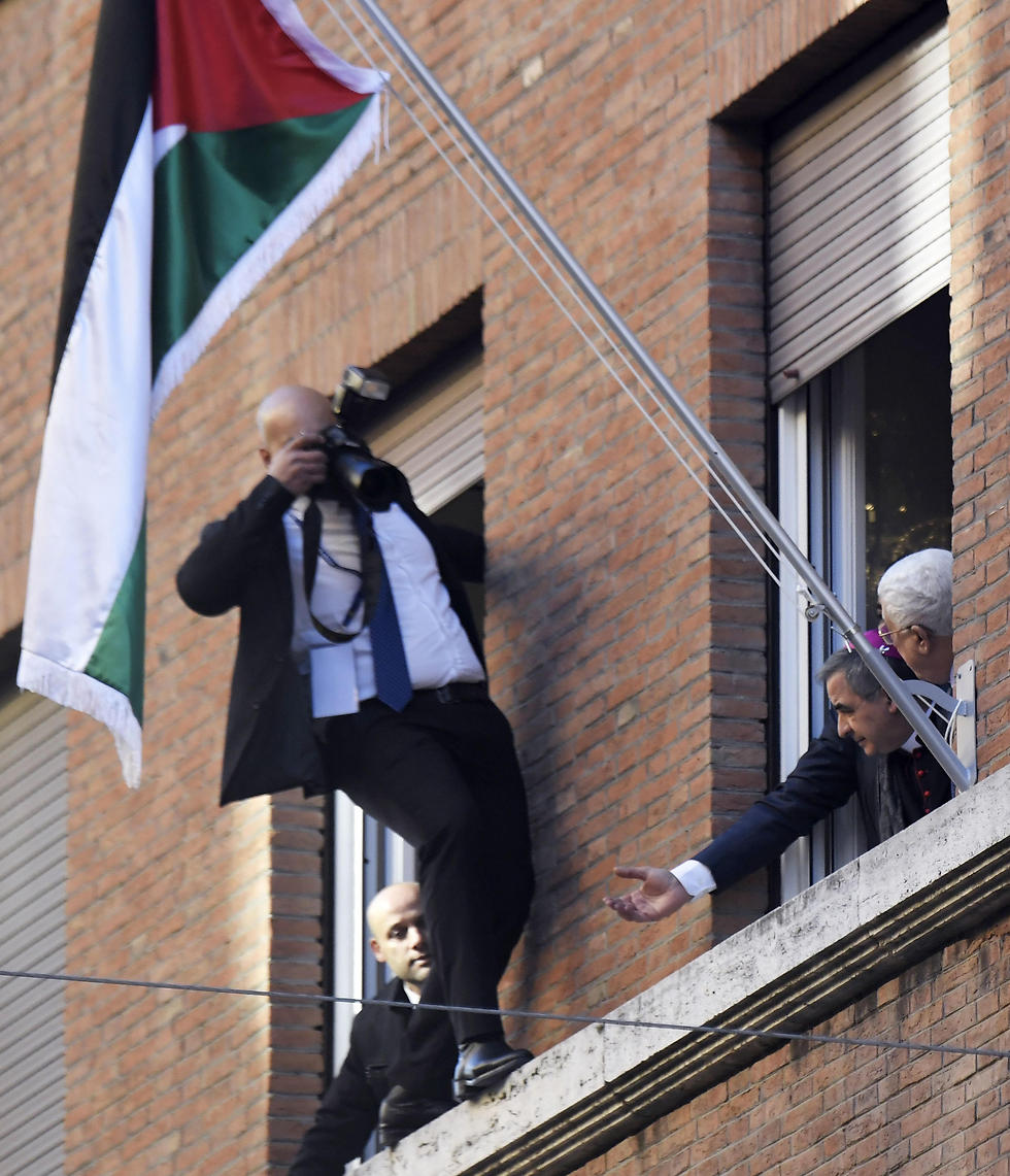 A photographer takes a picture as Abbas raises the Palestinian flag over the Palestinain Embassay to the Holy See (Photo: AFP)