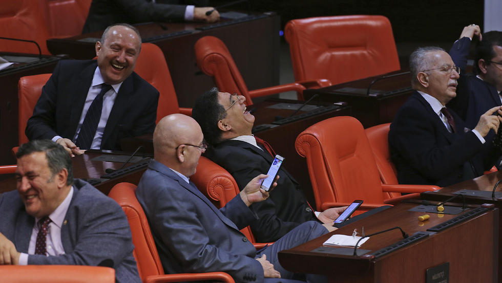Turkey's opposition Nationalist Movement Party, or MHP legislators, who declared that they voted 'No' , laugh during Turkey's parliament debate (Photo: AP)