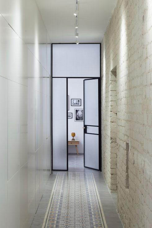 המסדרון נשאר ארוך כשהיה, אך עוצב מחדש. בקצהו הכניסה לחדר ההורים, מזכוכית ופרופילי ברזל, כך שנכנס לתוכו שפע של אור (צילום: גדעון לוין)
