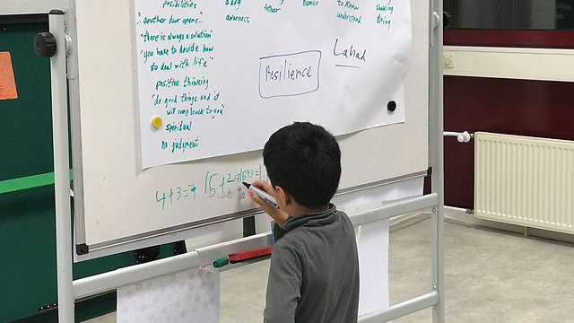 A Syrian boy makes use of the white board at the workshop for his studies