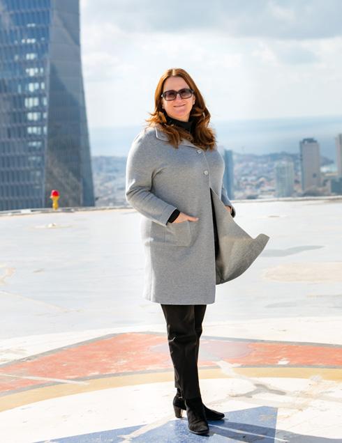 דנה עזריאלי על גג מגדל עזריאלי, כשמאחור מתנשא המגדל החדש: ''יש בו משהו שונה, הוא אלגנטי אבל עם ביטוי של עצמאות. במידה רבה כמו אשה חזקה, אשה מודרנית, שרוצה להיות אלגנטית ואיכותית. אני חושבת שהוא מאוד יפה'' (צילום: אינסה ביננבאום)