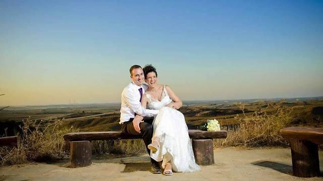 """אחיה של שני ואשתו ביום חתונתם במקום בו הכירו: מצפור לזכר אסף סיבוני ז""""ל (צילום: גדי סיארה)"""