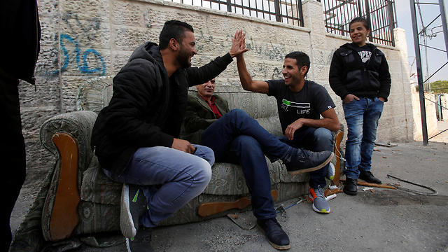 Yassin holds the hand of a Palestinian man as he is filmed in Aida refugee camp (Photo: Reuters)
