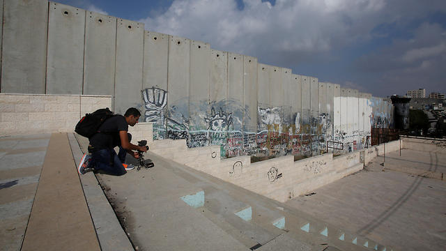 Filming near a section of the Israeli security barrier in Aida refugee camp (Photo: Reuters)