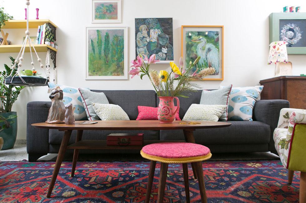 פינת הישיבה. הצבעים בציורי האם השפיעו על הבחירות, ואגרטל הפרחים גם הוא מנהג שירשה מאמה, שלמדה שזירת פרחים. ''אלה היו נוכחים אצלה תמיד במטבח, בפינת האוכל ובסלון'', מספרת הבת (צילום: שירן כרמל)